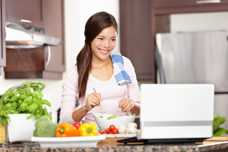Cooking woman looking at computer while preparing food in kitchen. Beautiful young multiracial woman reading cooking recipe or watching show while making salad. Stock Photo