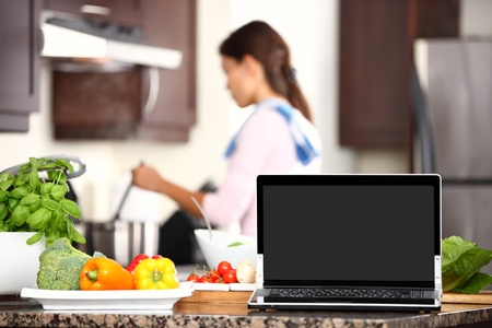 pc monitor: cooking and computer laptop concept. Blank pc monitor screen in focus with cooking woman in kitchen. Stock Photo