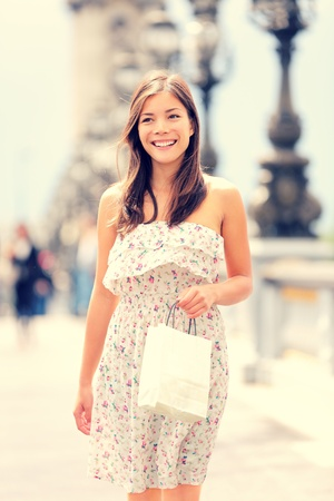 Paris woman walking with shopping bag in beautiful summer dress. Fresh natural interracial Asian Caucasian female model smiling happy in Paris, France walking on bridge over the Seine river. Archivio Fotografico
