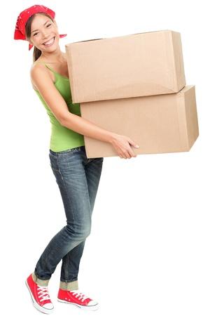 cajas de carton: Mujer que llevaba cajas de mudanza. Mujer joven mudanza a las nuevas cajas de cart�n en casa la celebraci�n de pie aislado en fondo blanco en toda su longitud. Foto de archivo