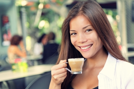 People on cafe - woman drinking coffee smiling at camera. Beautiful interracial Asian  Caucasian young woman enjoying typical spanish coffee called cortado. Banco de Imagens