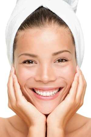 woman in towel: Spa beauty woman smiling close-up portrait. Beautiful genuine relaxed smile on young interracial Asian  Caucasian female beauty model wearing towel on head. White background. Stock Photo
