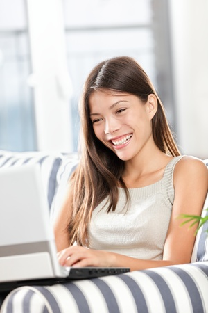 Woman using laptop computer smiling happy sitting in sofa. Pretty mixed race Caucasian Asian female model at home. photo