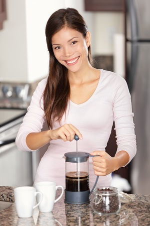 making coffee: woman making coffee in kitchen - french press coffee. Mixed race Asian Caucasian female model in her twenties at home.