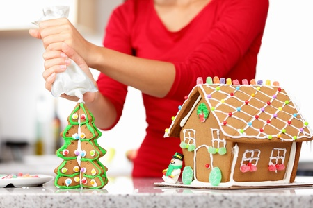 biscuit: gingerbread house. Woman in holidays preparations putting glazing on gingerbread house Christmas trees.