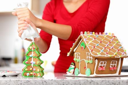 weihnachtskuchen: Lebkuchenhaus. Woman in Urlaub Vorbereitungen setzen Verglasung Lebkuchenhaus Weihnachtsbäumen.