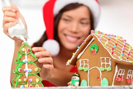 decoracion de pasteles: Chica haciendo la casa de pan de jengibre. Mujer joven en la preparaci�n de la Navidad poniendo hielo en la casa de pan de jengibre. Modelo que viste sombrero de santa.