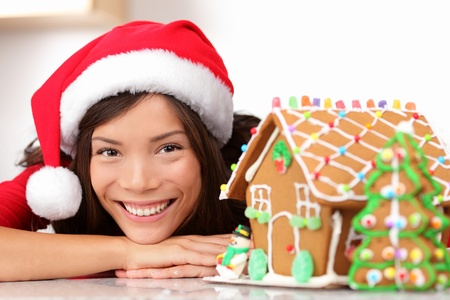 Christmas santa woman and gingerbread house. Cute young asian woman wearing santa hat.