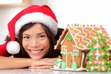 Kerst santa vrouw en peperkoek huis. Schattige jonge Aziatische vrouw met kerstmuts.