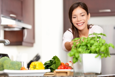 Woman making food in kitchen reaching for basil plant. Healthy eating concept with beautiful happy smiling multi-racial Caucasian / Asian woman at home. Banque d'images