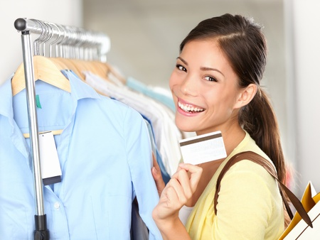 gastos: Shopping woman showing credit card or gift card by clothes rack. Happy smiling mixed race Caucasian  Asian female shopping in store.