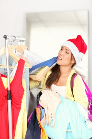 shopper: christmas shopping - woman tired. Funny image of woman exhausted from Christmas sales. Young Asian woman wearing Santa hat.