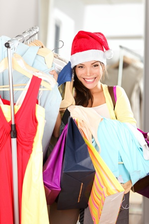 Christmas shopping sale. Woman buying clothing in clothes retailer wearing santa hat holding shopping bags. Beautiful Mixed Asian  Caucasian female model smiling happy at camera. photo