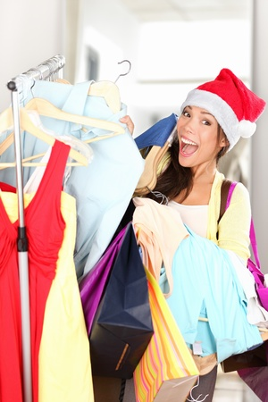 Christmas shopper excited. Shopping woman in retail store holding shopping bags wearing red santa hat. Beautiful multi-racial Asian / Caucasian female model smiling happy and cheerful at camera. photo