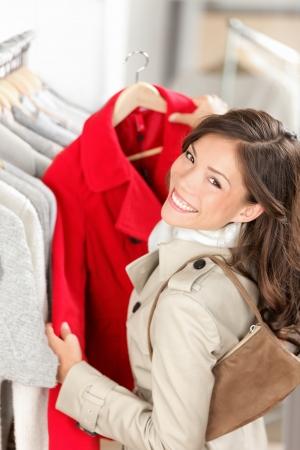 재킷: 쇼핑. 여자 구매자 옷 가게에서 재킷  코트를 찾고 있습니다. 아름 다운 미소 젊은 여자 - 혼합 된 레이스 아시아  백인 스톡 사진