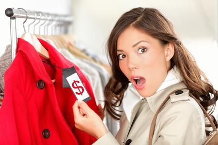 kledingwinkel: winkelen vrouw geschokt en verrast over de prijs te kijken naar prijskaartje aan jas of vest. Vrouw shopper winkelen voor kleding binnen in kledingzaak. Grappig beeld van Aziatische  Kaukasische vrouwelijk model. Stockfoto
