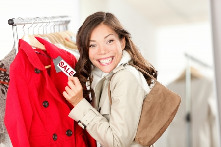 Shopping woman excited showing price tag at clothes sale in clothing store. Smiling cheerful woman. Price label reads sale. Archivio Fotografico