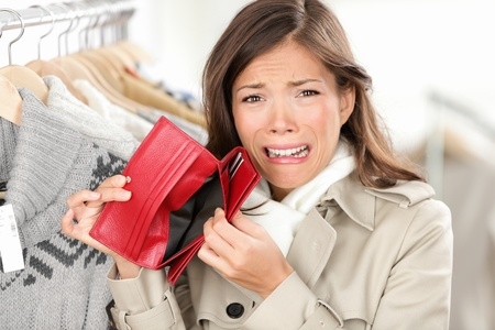 wallet: empty wallet - woman with no money in purse shopping. Female shopper in clothes store upset crying as she is out of money. Funny image of mixed race Caucasian  Asian woman. Stock Photo