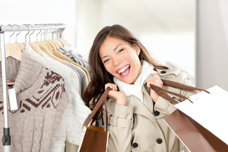 buying: Shopper woman happy shopping buying clothes.  Joyful excited smiling woman - mixed race Caucasian  Chinese Asian female model holding shopping bags in trench coat inside in clothing store. Stock Photo