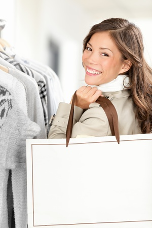 happy shopping: Shopper woman showing shopping bag with copy space. Smiling Caucasian  Chinese Asian female model buying clothes in clothing store. Stock Photo