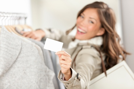 Shopping gift card sign. Woman shopper showing empty blank sign in clothing store. Beautiful excited smiling asian caucasian female model.