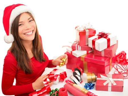 Christmas gift wrapping woman wrap presents during Christmas preparations. Cute smiling happy asian / caucasian girl wearing santa hat. Isolated on white background. Archivio Fotografico