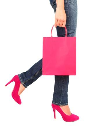 piernas con tacones: Compras concepto. Bolsa de la compra, jeans, zapatos de tac�n alto y de cerca, con copia espacio en la bolsa de compras. Perfil de la mujer de compras cerca aisladas sobre fondo blanco, una bolsa de color rosa  rojo y unos zapatos.