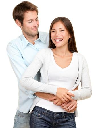 pareja abrazada: Pareja joven sonriendo feliz. Pareja interracial, mujer asi�tica, de raza cauc�sica hombre aislado sobre fondo blanco.
