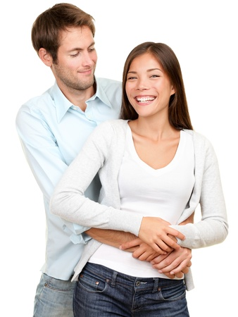 young couple smiling happy. Interracial couple, Asian woman, Caucasian man isolated on white background. Stock Photo