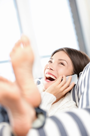 Woman talking and laughing on smart phone. Asian woman having fun conversation on mobile cell phone sitting comfortable in sofa home in living room.