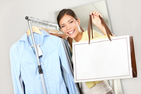 Shopper woman showing shopping bag sign with copy space for text. Woman standing by clothes rack in clothing store. Happy smiling multiracial Caucasian / Asian female model.
