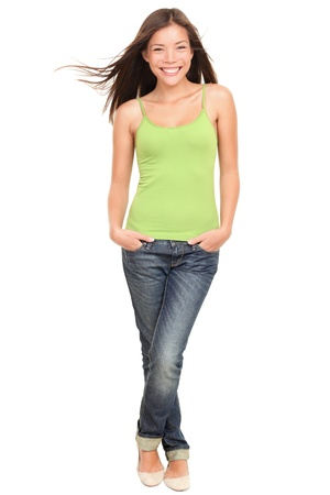 Woman. Asian woman model standing happy and smiling. Fresh portrait of a young beautiful mixed race Caucasian / Asian female model in full length isolated on white background. Archivio Fotografico