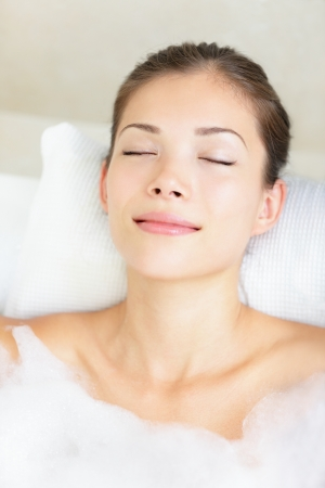 closed eyes: Woman in bath relaxing. Closeup of young asian woman in bathtub bathing with closed eyes.