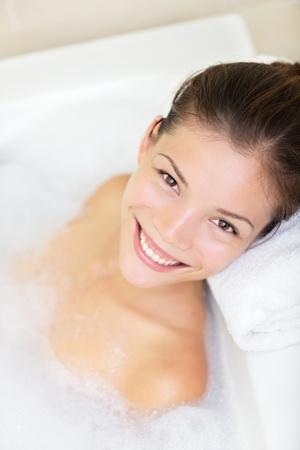 lying in bathtub: bathtub woman smiling happy bathing with bath foam. Beautiful mixed race Caucasian and Asian female model enjoying bath.