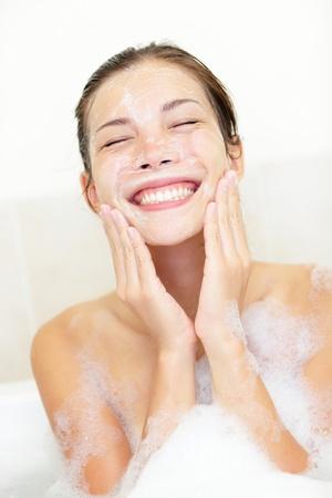 얼굴 표정: 얼굴 세척. 거품 목욕에 얼굴을 세척하는 여자. 욕조에 그녀의 얼굴을 청소 젊은 아시아  백인 여자는 행복 미소.