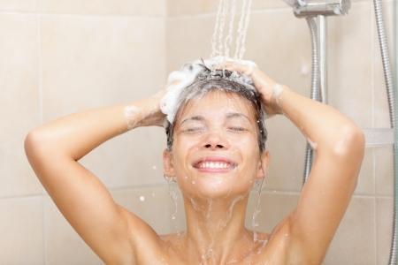champu: Mujer en la ducha, lavar el pelo con champú. Hermosa mujer ducha lavado de pelo largo con salpicaduras de agua. Morena modelo femenino multirracial en la ducha.