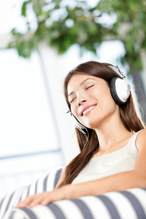 listening to people: woman listening to music in headphones relaxed and serene. Cute beautiful girl sitting alone in sofa at home Stock Photo