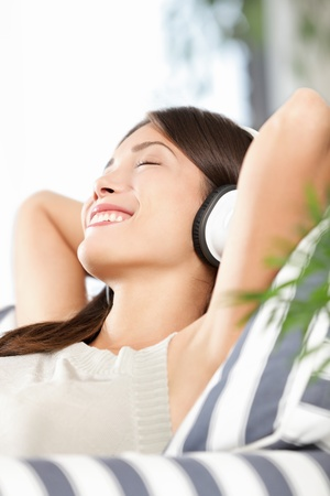 Headphones woman listening to music enjoying and relaxing. Relaxed beautiful multiracial Chinese Asian Caucasian female model in sofa in living room.