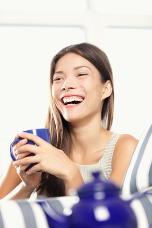 Woman laughing drinking tea, relaxing at home in couch. Smiling happy mixed race Caucasian Asian female model in living room. photo