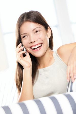 llamando: Mujer asiática hablando por teléfono inteligente riendo y casa de descanso en el sofá. Smilng alegre hermosa mujer multirracial feliz.