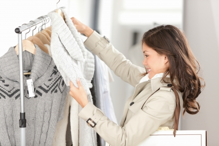 coat rack: Woman shopping clothes. Shopper looking at clothing indoors in store. Beautiful happy smiling asian caucasian female model. Stock Photo