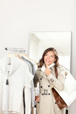 coats: Shopping woman thinking inside in clothing store. Happy smiling shopper looking up at copy space. Beautiful mixed race Caucasian  Chinese Asian female model holding shopping bags in shop. Stock Photo