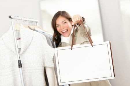 Shopping woman showing shopping bag sign with copy space. Shopper looking for clothes indoors in clothing store. Beautiful happy excited and smiling mixed race Asian Caucasian female model inside. Archivio Fotografico