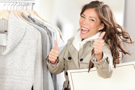 kledingwinkel: Shopper vrouw gelukkig te winkelen en het kopen van kleding. Joyful opgewonden lachende vrouw - gemengd ras Kaukasisch  Aziatisch Chinese vrouwelijk model bedrijf boodschappentassen in de vacht binnen in kledingzaak geven thumbs up. Stockfoto