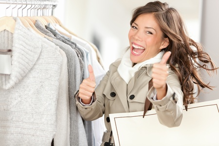 female clothing: Shopper woman happy shopping and buying clothes. Joyful excited smiling woman - mixed race Caucasian  Chinese Asian female model holding shopping bags in coat inside in clothing store giving thumbs up. Stock Photo