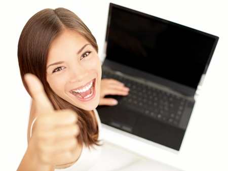 thumb's up: Laptop woman happy giving thumbs up success sign sitting at computer PC with excited face expression. Beautiful smiling cheerful multiracial Asian Caucasian student girl on white background. Stock Photo