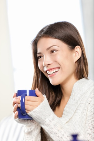 Woman sitting drinking tea or coffee smiling happy. Pretty mixed race Caucasian / Chinese Asian female model at home. photo