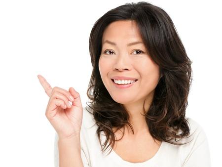 아시아 여자 보여주는 가리키는. 가리키는 행복 미소 보여주는 가운데 세 중국 아시아 여자. 그녀의 50 대 초반의 여성 모델 흰색 배경에 고립입니다. 스톡 콘텐츠