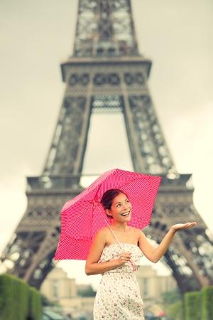 lloviendo: Torre Eiffel de París la mujer. Linda hermosa mujer joven en traje de pie sonriendo feliz con paraguas rojo en la parte delantera de la torre Eiffel, París, Francia. Modelo femenino asiático  caucásico.