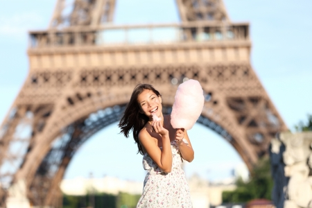 tourist destination: Paris Eiffel Tower woman smiling happy and cheerful eating cotton candy in front of Eiffel Tower in Paris, France. Cute Asian  Caucasian girl.